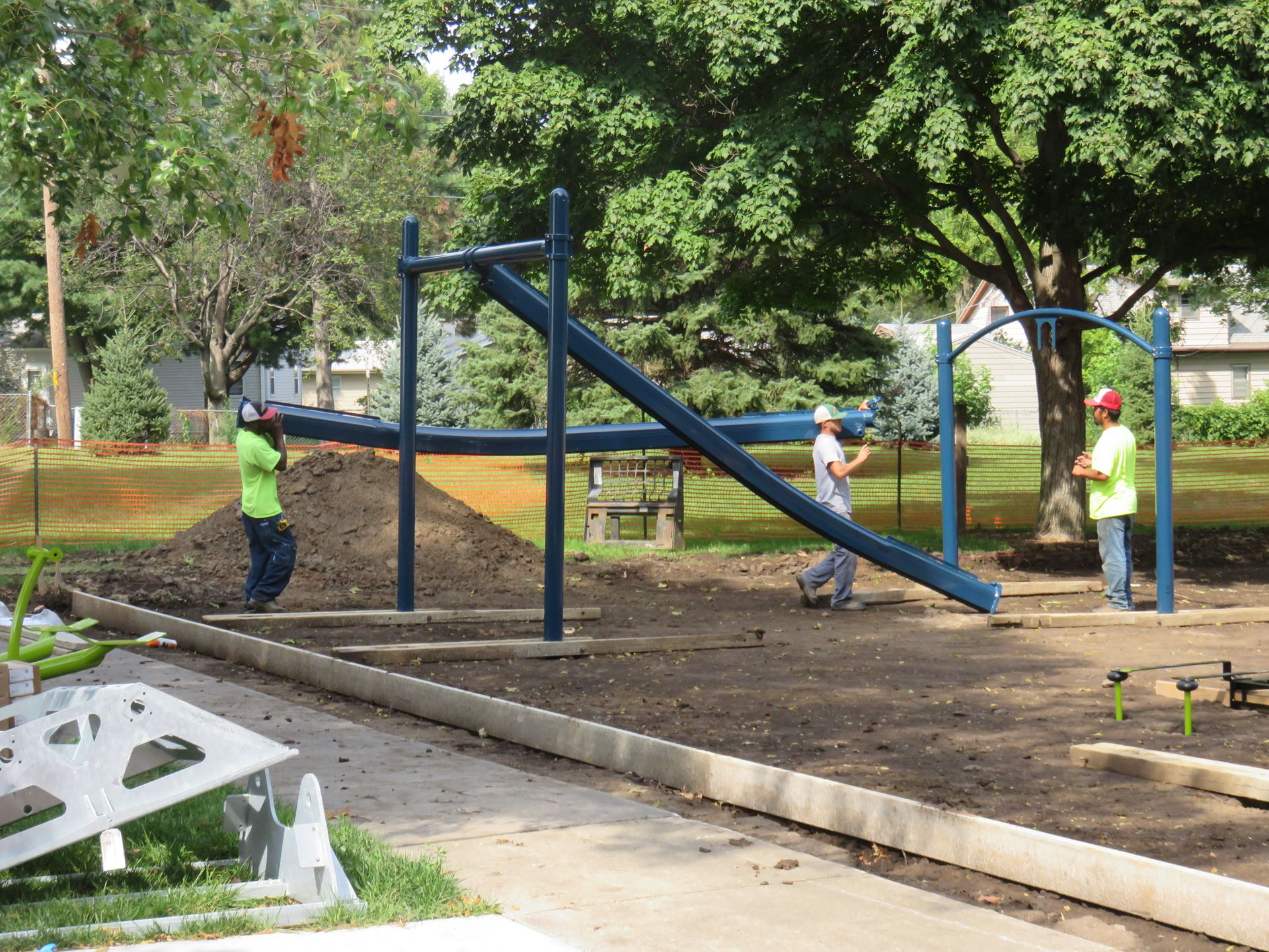 workers setting up play equipment at site