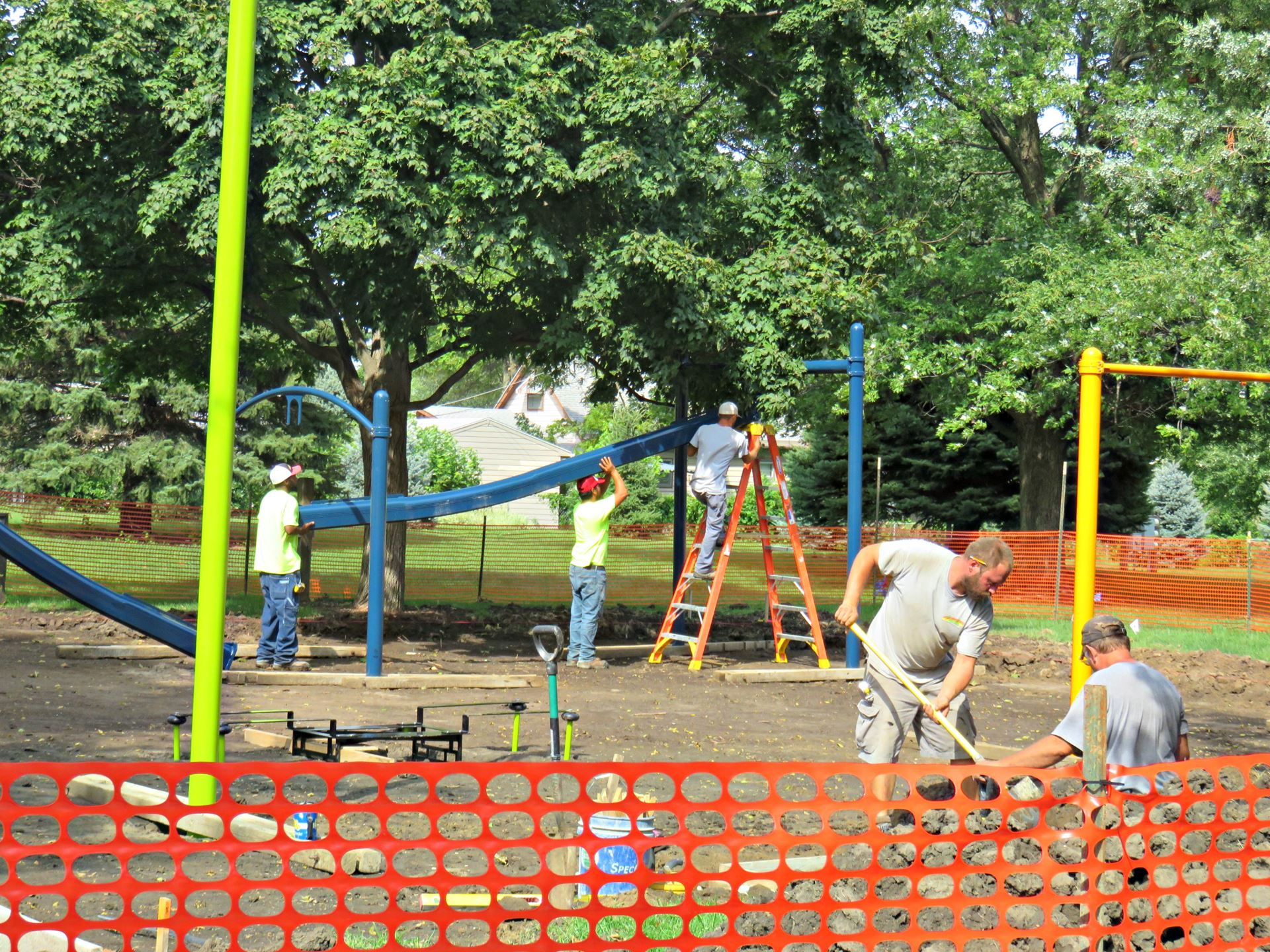 workers setting up play equipment while other workers are digging at site