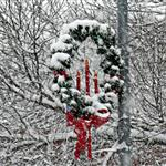 Christmas Wreath covered with snow on pole
